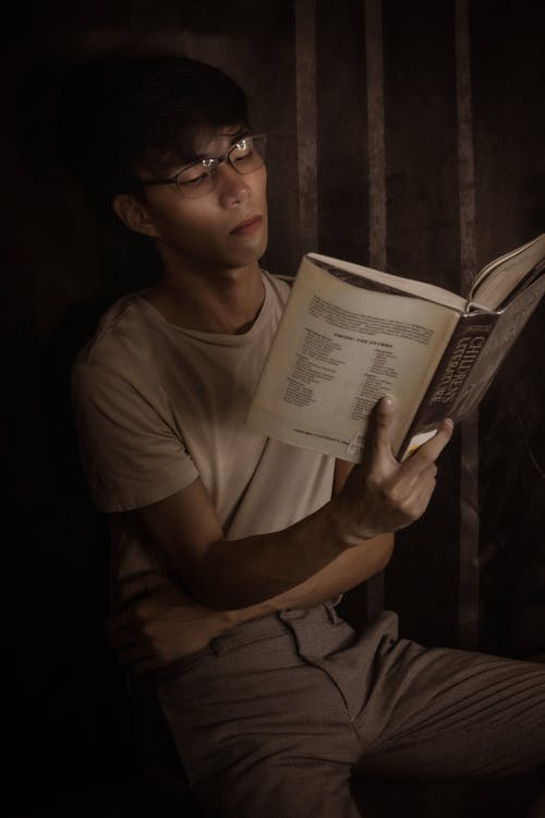 Pensive Asian male reading book at home