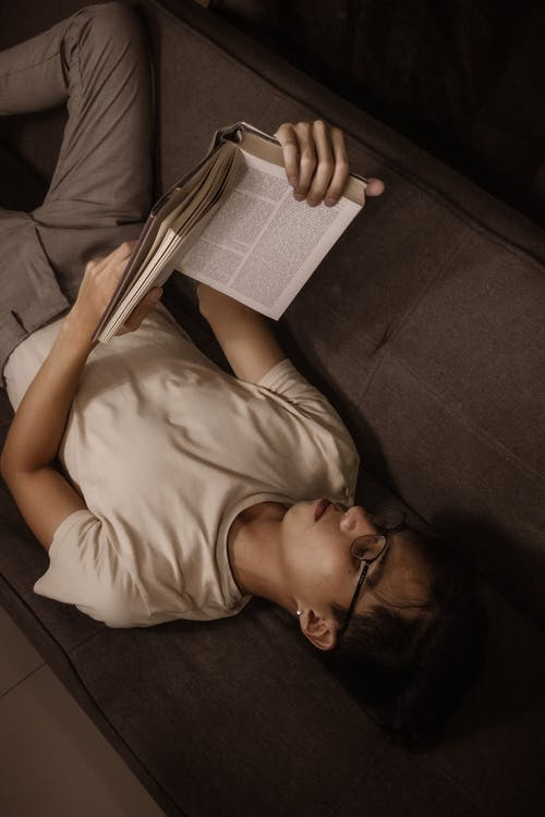 From above of concentrate guy in casual outfit and eyeglasses lying on comfortable sofa and reading book in dark room at home
