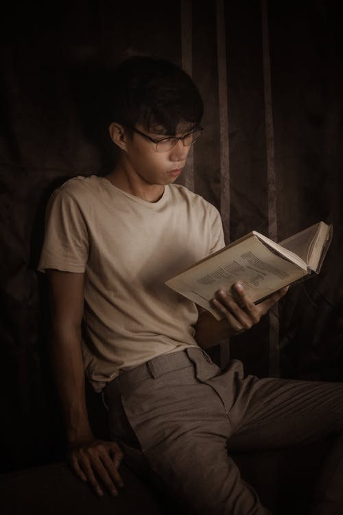 Thoughtful Asian male in eyeglasses and casual clothes sitting and reading book in dark room