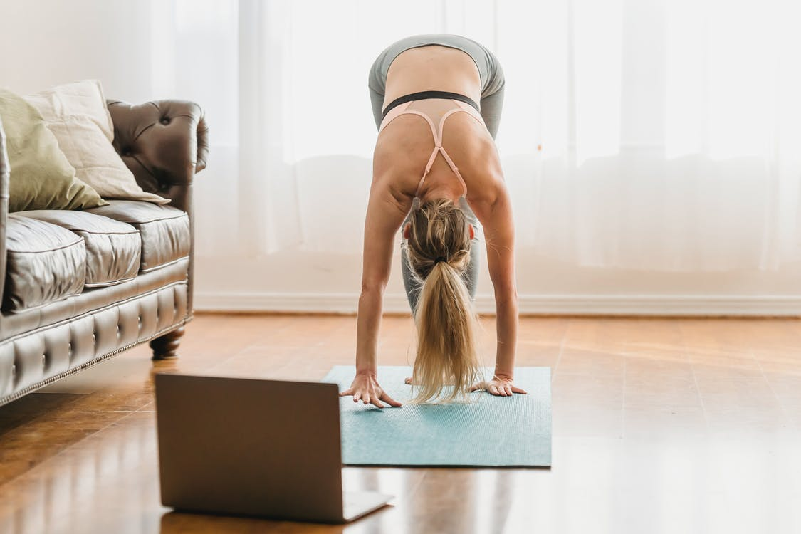 Full body of unrecognizable female in activewear performing standing forward bend asana while standing on mat near laptop during online yoga lesson at home