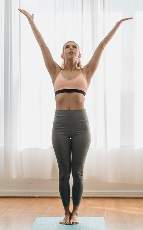 Full body of mountain pose with raised arms looking up while standing on mat during yoga training in light room