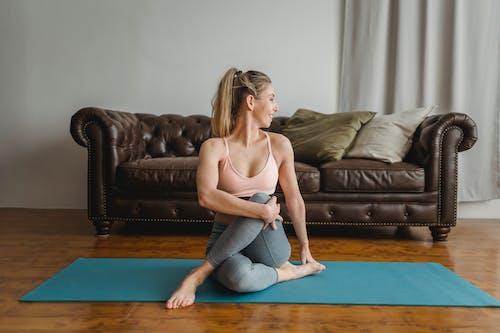 Fit woman practicing yoga while doing ardha matsyendrasana posture