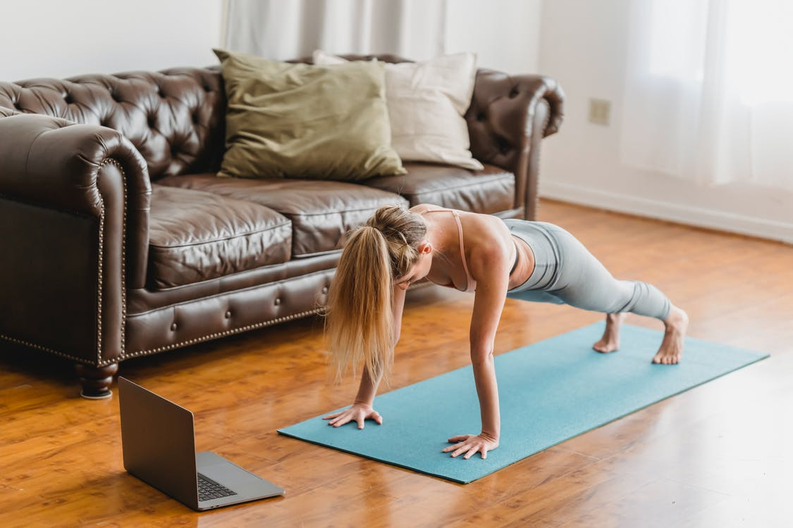 Side view full body of sportive female in activewear practicing kumbhakasana asana on mat near laptop during online lesson in living room near couch