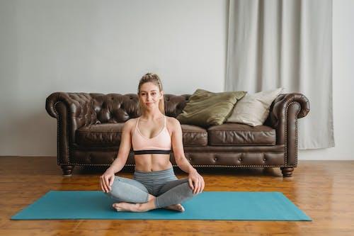 Sporty woman doing half lotus pose