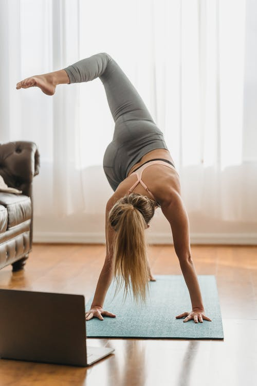 Full body of faceless barefoot female in sportswear performing eka pada svanasana posture on mat near laptop during online yoga training