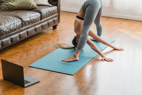 Full body side view wide legged forward bend asana while training on mat in living room with laptop near couch