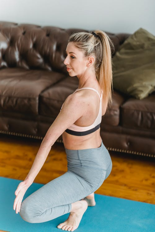Full bode side view of active female in sportswear exercising garland posture on mat near couch in living room during yoga training