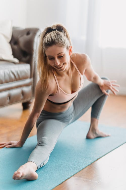 Full body of positive young woman wearing leggings and sportive bra stretching legs on blue yoga mat near leather couch in light living room near curtains