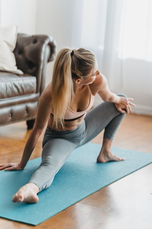 Lady in activewear stretching legs on yoga mat in apartment