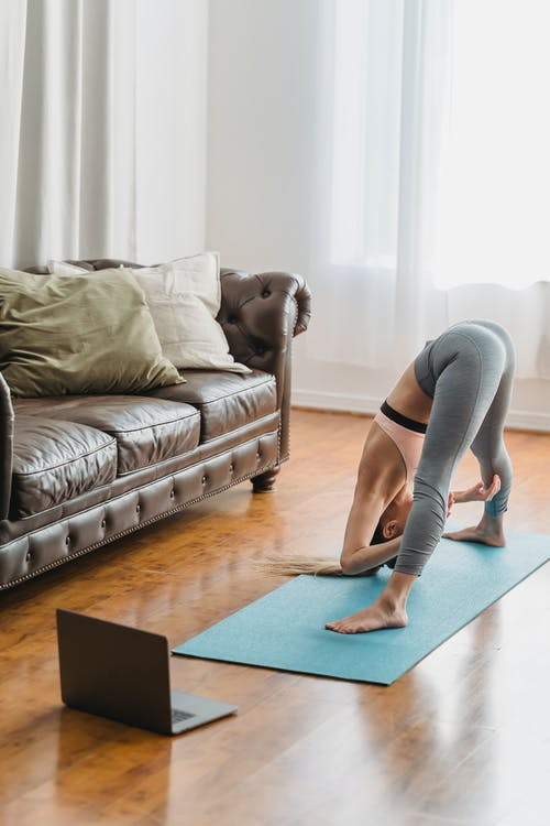 Faceless lady in activewear stretching back at home near laptop