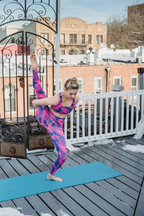 Flexible woman stretching on terrace