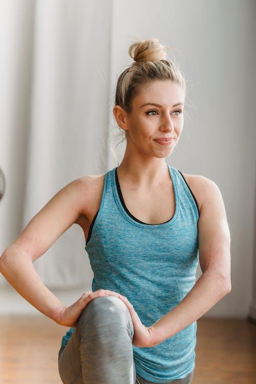Cheerful woman in sportswear practicing yoga