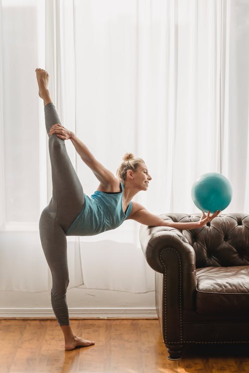 Full body of flexible female gymnast with blue ball in hand practicing vertical split stretching near leather sofa