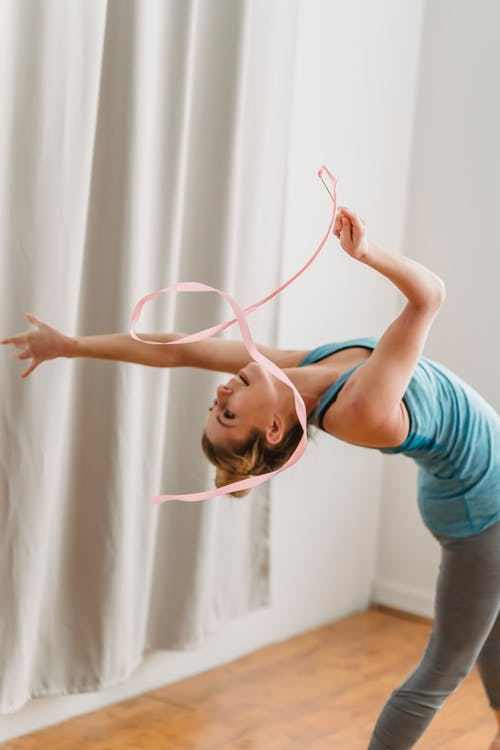 Young woman doing back bend exercise with gymnastic ribbon