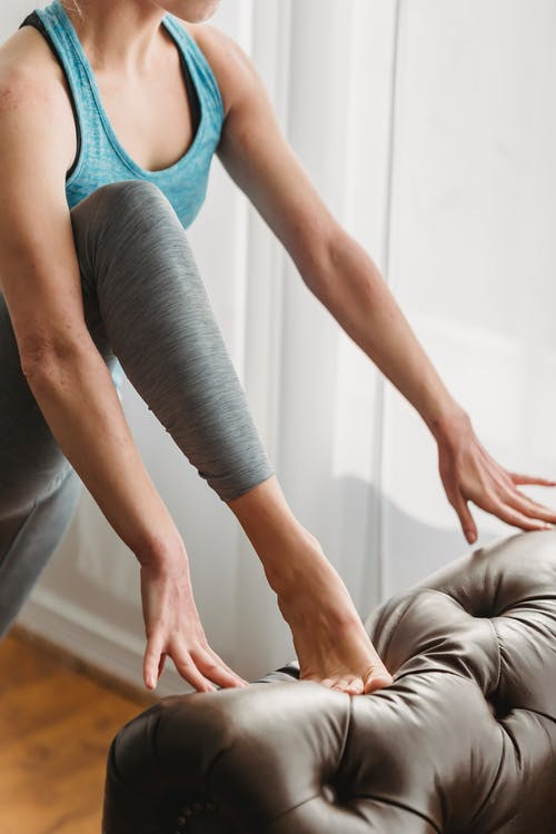 Woman doing stretching exercise during training at home