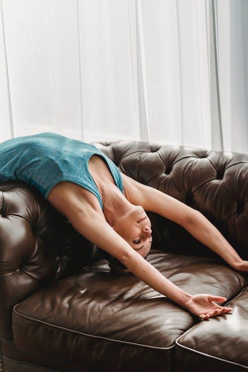 Vrouw Die In Blauw Mouwloos Onderhemd Op Bruine Leerlaag Ligt