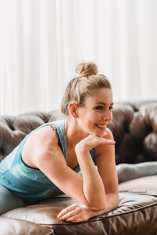 Cheerful woman doing split on sofa