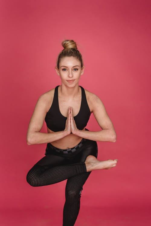 Barefoot sportswoman in activewear performing Ardha Padmasana with namaste gesture against pink background and looking at camera