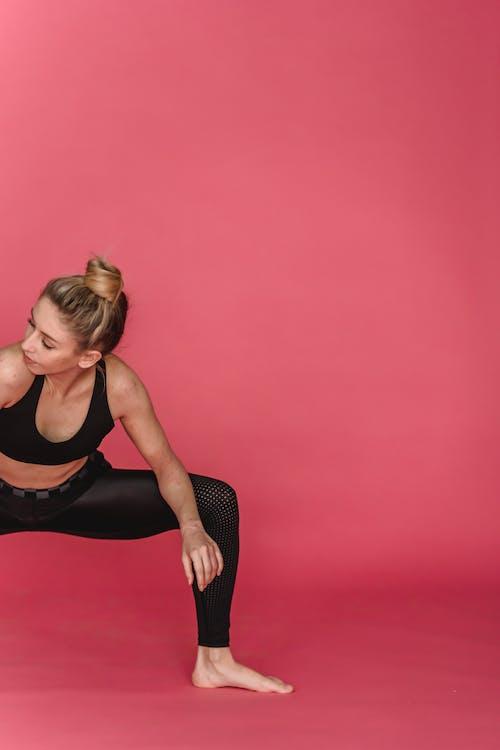 Flexible sportswoman squatting for stretching legs in studio