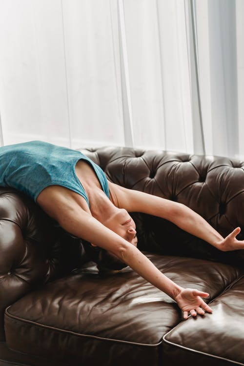 High angle of female in activewear doing back bend while stretching body on sofa