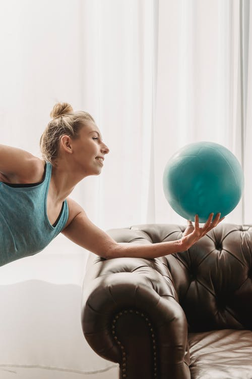Smiling woman doing exercise with fitness ball