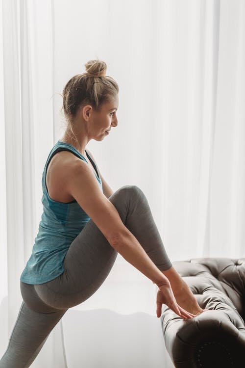 Fit woman doing stretching exercise with leg on sofa