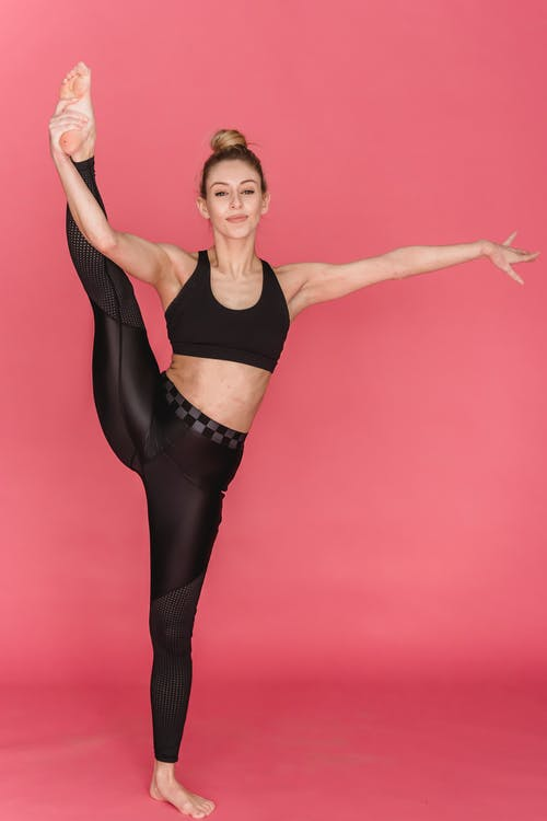 Full body of barefoot flexible female athlete in sportswear performing standing split with hand outstretched against pink background