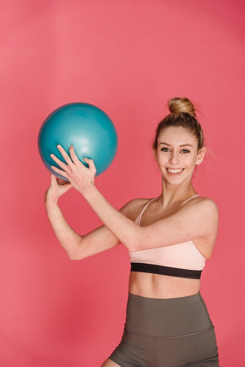 Positive female athlete wearing sportswear practicing exercises with fitness ball against pink background and looking at camera