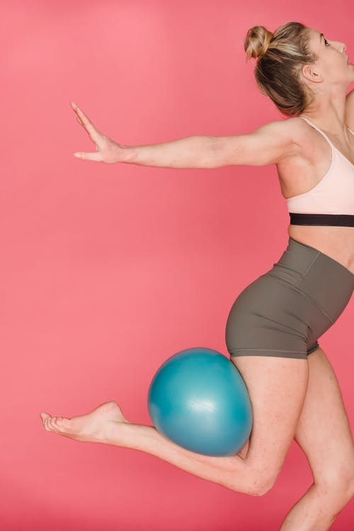 Slim woman training with fitness ball in studio