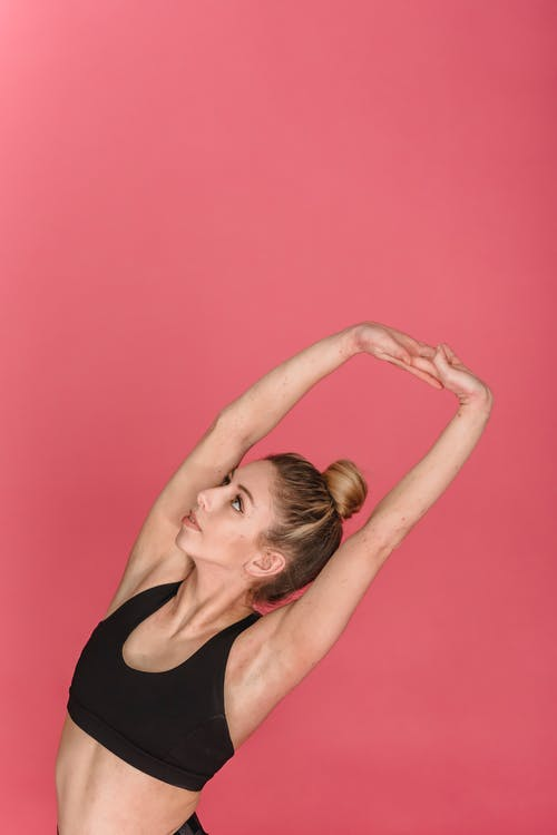 Fit female athlete with hands raised above head stretching body during training against pink background
