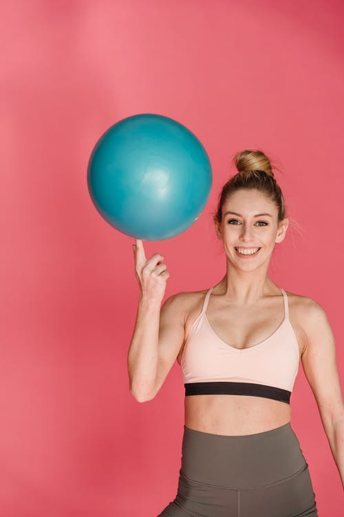 Smiling woman standing with fitness ball on finger