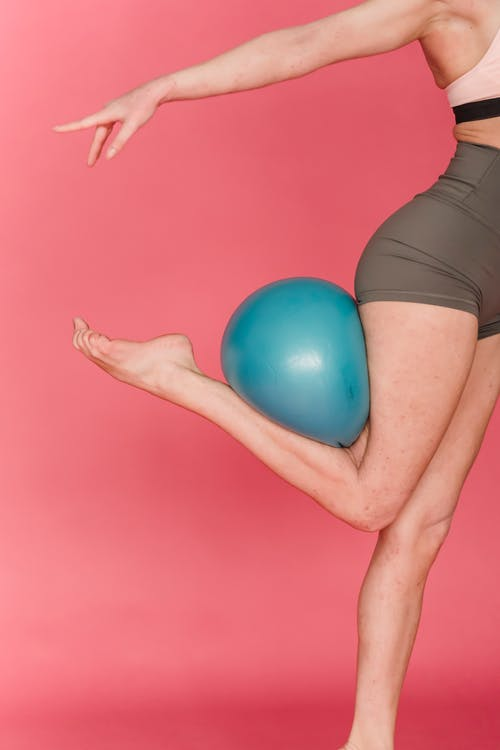 Side view of slim faceless female gymnast with fitness ball stretching tiptoes against pink background