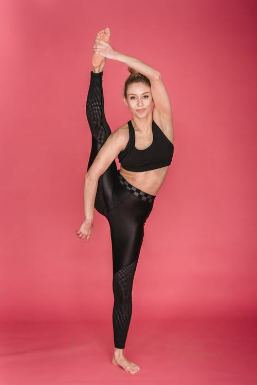 Full body of flexible female athlete performing vertical split against pink background and looking at camera