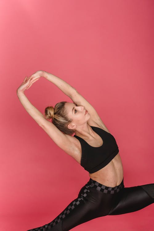 Fit woman doing lunge with hands up