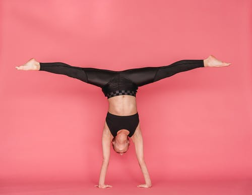 Flexible woman stretching legs while standing on hands