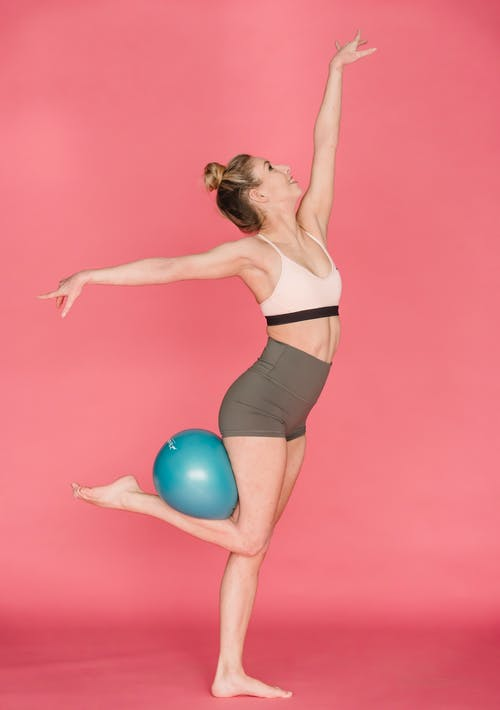 Side view full body of graceful positive female athlete outstretching arms while standing with fitness ball on leg against pink background