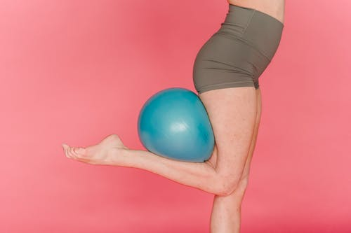 Slender woman exercising with fitness ball in studio