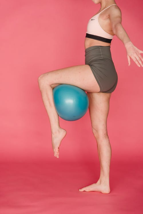 Woman in Black Shorts Holding Blue Exercise Ball