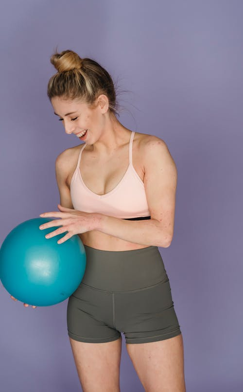 Fit positive gymnast with blue shiny ball