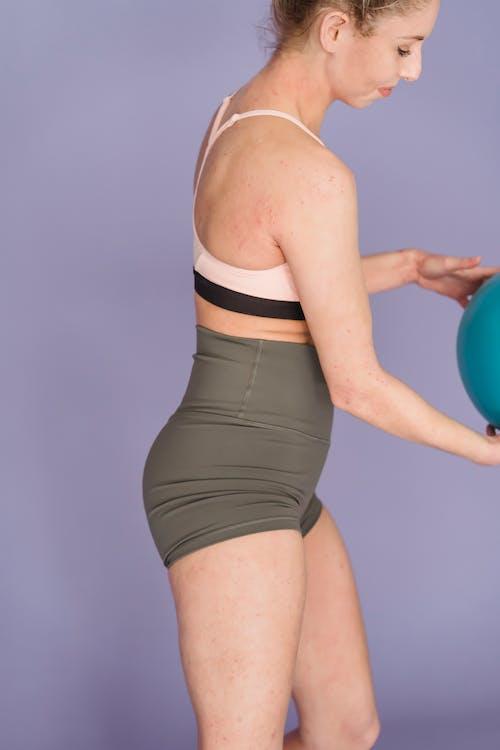 Slim woman exercising with gym ball