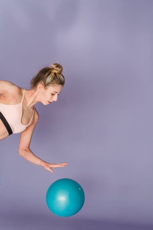 Slim sporty woman practicing with gym ball