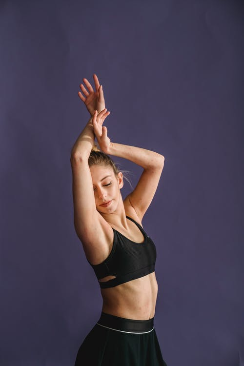 Graceful slender gentle female with eyes closed in activewear raising arms on purple background