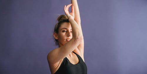 Graceful woman with bun on head and arms raised dancing