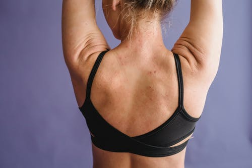 Back view of crop anonymous female with muscular arms on purple background of studio