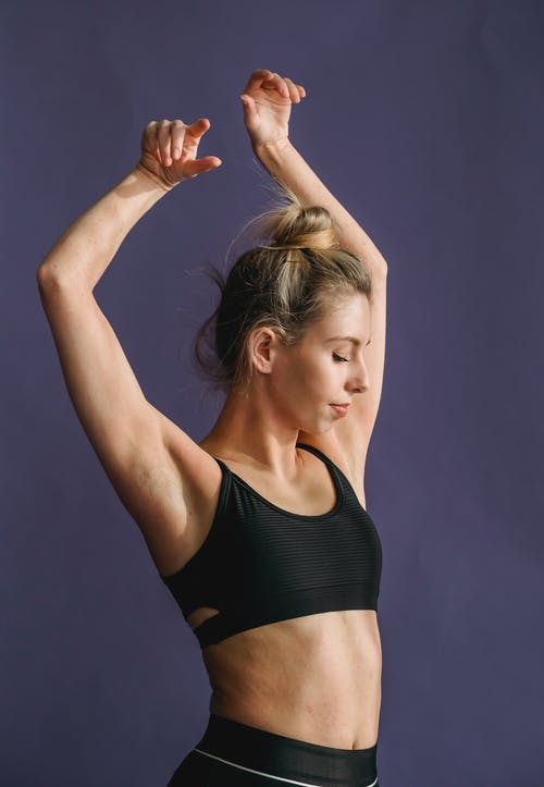 Fit woman in active outfit dancing