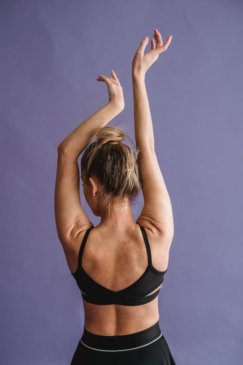 Back view of anonymous slim female with graceful arms raised dancing on purple background