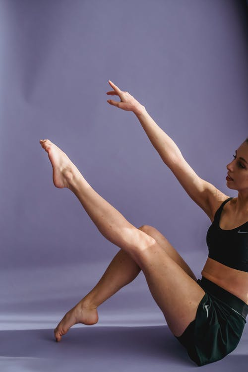 Woman sitting on floor and raising arm and leg in studio