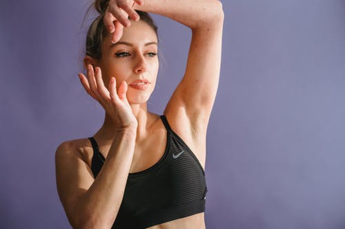 Tranquil slim young woman in black sportive bra standing with raised arms and looking away against purple background in studio
