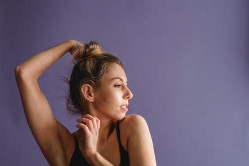 Calm female thoughtfully looking away against purple background in studio