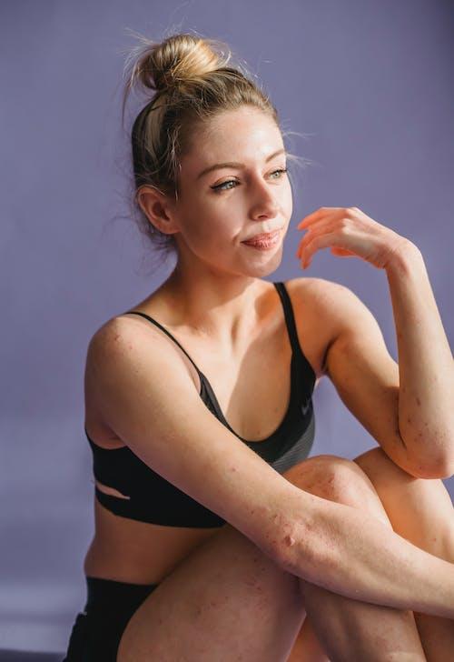 Thoughtful female in underwear sitting in light studio